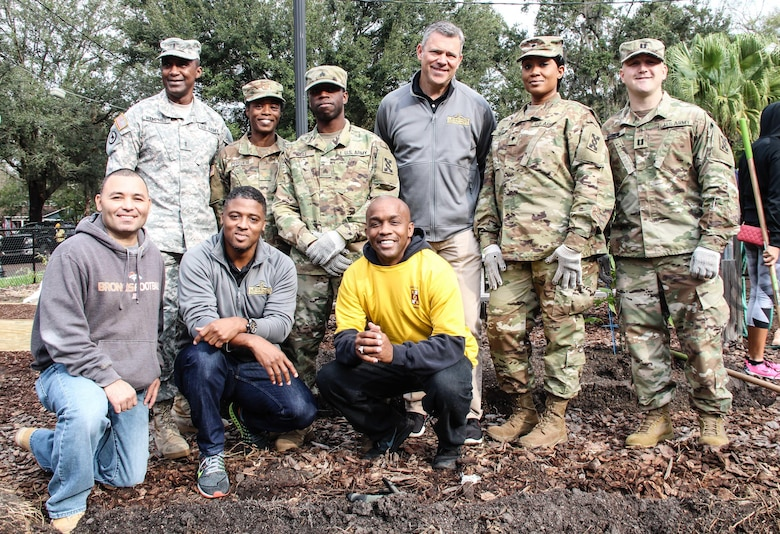 Soldiers from the 143d Sustainment Command (Expeditionary) pose for a group photo with National Football League legends Mark Brunell (top row, third from right) and Warrick Dunn (bottom row, second from left) Jan. 27, 2017, at the Colonialtown North Community Garden in Orlando, Fla. The Army Reserve and the NFL joined forces to lighten the environmental impact produced the first ever Pro Bowl to take place in Orlando by bringing one of the city's oldest community gardens back to its former, greener glory. The players and Soldiers worked side-by-side with scores of other volunteers from Central Florida to pour mulch, plant trees, repair fences and build garden beds.