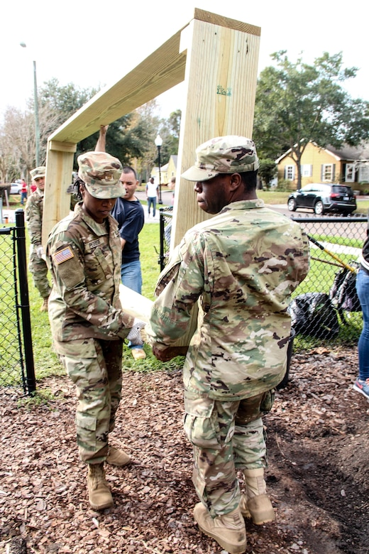 Army Sgt. Jonathan Bell (front), an Orlando, Fla., native serving as a human resources noncomissioned officer, Headquarters & Headquarters Company, 143d Sustainment Command (Expeditionary), and Army Maj. Diana Peguese, chief of public affairs, 143d ESC, carry a newly constructed garden bed into the Colonialtown North Community Garden Jan. 27, 2017, in Orlando, Fla. The Army Reserve and the NFL joined forces to lighten the environmental impact produced the first ever Pro Bowl to take place in Orlando by bringing one of the city's oldest community gardens back to its former, greener glory. The players and Soldiers worked side-by-side with scores of other volunteers from Central Florida to pour mulch, plant trees, repair fences and build garden beds. U