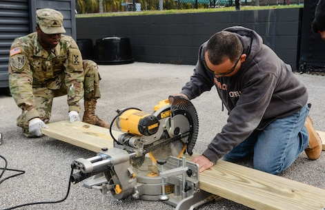 Army Warrant Officer Candidate Brian M. Torres (right), a Vineland, N.J., native who recently entered the warrant officer candidate program while serving in the 143d Sustainment Command (Expeditionary)'s G6 (Communications) section, operates a chop saw while Army Sgt. Jonathan Bell (left), an Orlando, Fla., native serving as a human resources noncomissioned officer, Headquarters & Headquarters Company, 143d ESC, holds the wooden board in place during a an environmental sustainability community project Jan. 27, 2017, in Orlando, Fla. Bell, Torres and five other Army Reserve Soldiers constructed several wooden garden beds to help revive  Orlando's Colonialtown North Community Garden to its former, greener glory. Directed by Green Works Orlando in conjunction with the NFL's Environmental Program, the garden's revival was one of the many community projects both organizations managed to lighten the environmental footprint produced by the tens of thousands of football fans who have flocked to The City Beautiful to watch the NFL's first Pro Bowl game to take place in the Continental U.S. since 1979.