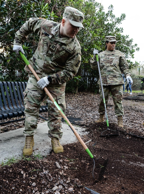 Army Capt. Josh C. Agnew (left), a Chippewa Falls, Wisc., native serving operations officer, 143d ESC, rakes mulch and soil in preparation for the installation of a new garden bed at the Colonialtown North Community Garden Jan. 27, 2017, in Orlando, Fla. Agnew and six other Army Reserve Soldiers joined scores of volunteers from the Orlando community to help bring the garden back to its former, greener glory. Directed by Green Works Orlando in conjunction with the NFL's Environmental Program, the garden's revival was one of the many community projects both organizations managed to lighten the environmental footprint produced by the tens of thousands of football fans who have flocked to The City Beautiful to watch the NFL's first Pro Bowl game to take place in the Continental U.S. since 1979.