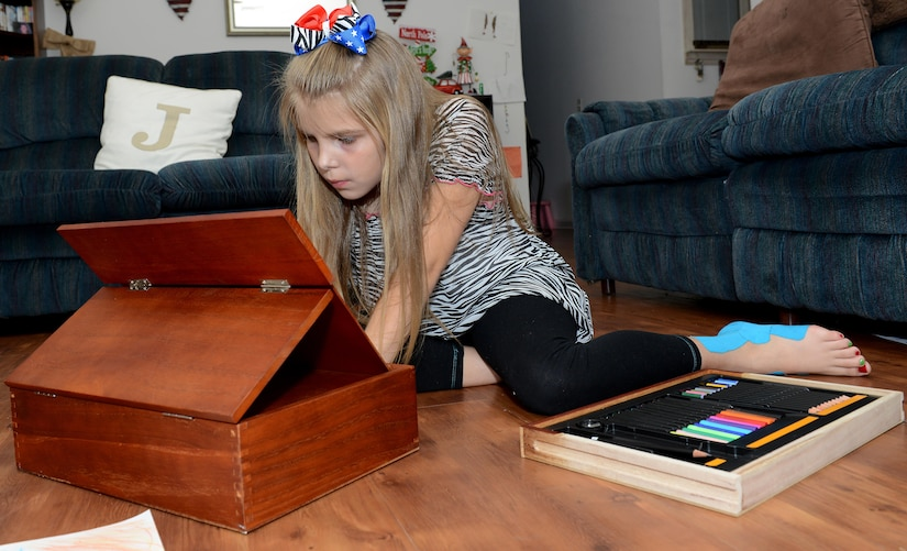 Eveylynn Johns, age nine, daughter of U.S. Army Sgt. Matthew Johns, 221st Military Police Detachment military police officer, draws with an art set in her home at Joint Base Langley-Eustis, Va., Jan. 5, 2017.  Eveylynn has been diagnosed with a genetic disorder called Ehlers-Danlos Syndrome, as well as postural orthostatic tachycardia syndrome. (U.S. Air Force photo by Staff Sgt. Teresa J. Cleveland)