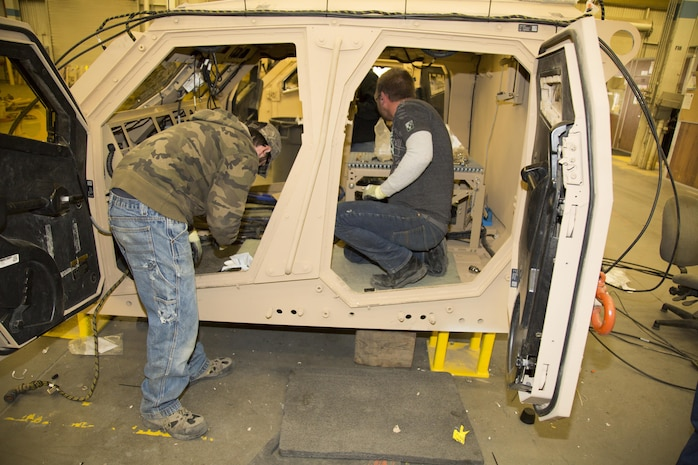 (Left) Kevin Leonard, a native of Newport Beach, Calif., and William Marler, from Victorville, Calif., heavy mobile equipment mechanics, work on the interior of the crew capsule for the M-ATV, also known as a Mine Resistant Ambush Protected All Terrain Vehicles, at Production Plant Barstow, Marine Depot Maintenance Command, Jan. 12. The crew cab is heavily protected by reinforced armor to help the occupants survive a blast from powerful improvised explosive devices.