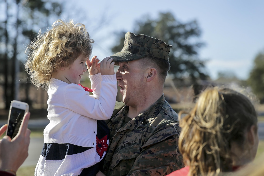 A Marine embraces his family