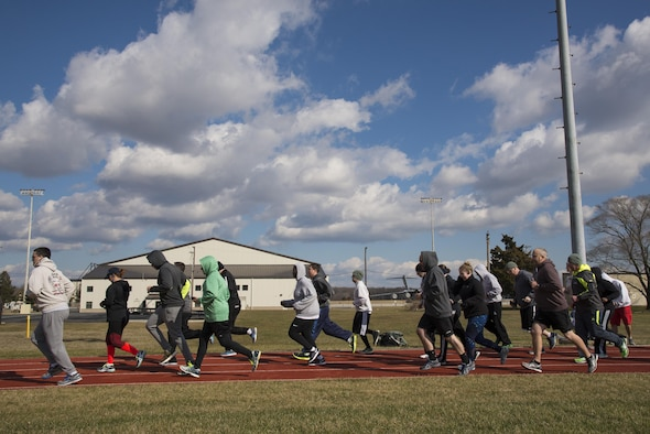 Members of Team Dover run a warmup lap Jan 30, 2017, during a 90 Plus class at the track on Dover Air Force Base, Del. Each high-intensity class only lasts about 20 to 30 minutes, and focuses on improving performance in each area of the fitness assessment. (U.S. Air Force photo by Senior Airman Aaron J. Jenne)