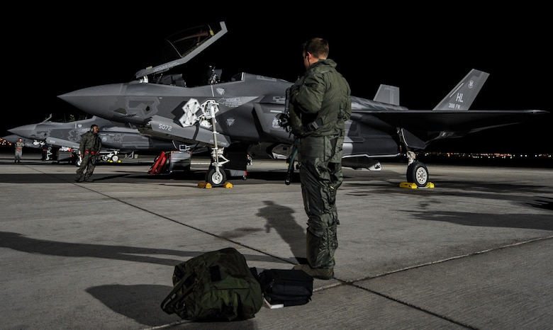 A pilot assigned to the 388th Fighter Wing, Hill Air Force Base, Utah, stands by an F-35A as preflight checks are performed before a night operation Red Flag 17-1 on Nellis Air Force Base, Nev., Jan. 24, 2017. This is the first time that F-35A crews integrate with other airframes during a Red Flag exercise. (U.S. Air Force photo by Airman 1st Class Kevin Tanenbaum/Released)
