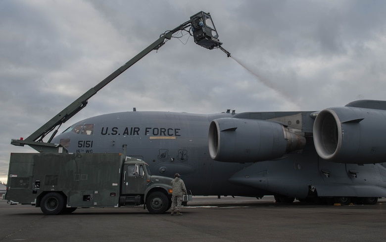 Maintainers from the 821st Contingency Response Group, deice a C-17 Globemaster III aircraft from Joint Base Pearl Harbor-Hickam, Hawaii, before taking off, Jan. 24, 2017, at Joint Base Lewis-McChord, Washington. With temperatures well below freezing the deicer is used to provide protection of aircraft surfaces, engines and aircraft sensors from the elements. (U.S. Air Force photo by Staff Sgt. Robert Hicks)