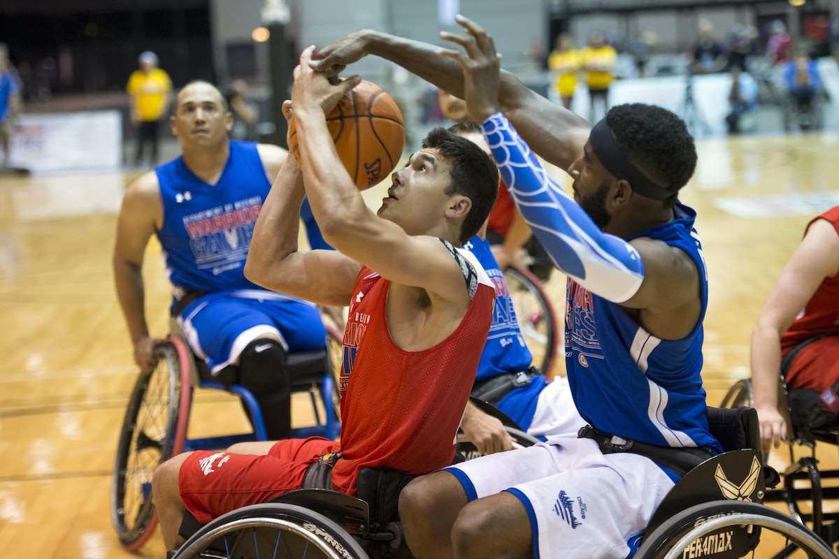 Marine Corps Lance Cpl. Robert Anfinson Jr. battles three other players for a rebound during wheelchair basketball.
