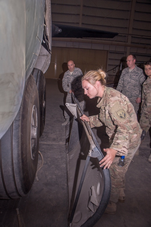 Airman Kiley Foulke, a 386th Expeditionary Maintenance Squadron combat metals team member, inspects the edge of a recently repaired C-130 landing gear door during an installation operation at an undisclosed location in Southwest Asia, June 23, 2017.  (U.S. Air Force photo by Master Sgt. Eric M. Sharman)