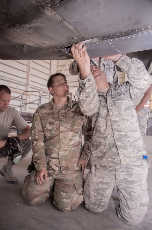 Master Sgt. Daniel Taylor, 386th Expeditionary Maintenance Squadron combat metals flight chief, checks a newly repaired C-130H landing gear door for fit after installation as Senior Airman Andrew Williams, a combat metals team member, looks on during an installation operation at an undisclosed location in Southwest Asia, June 23, 2017. (U.S. Air Force photo by Master Sgt. Eric M. Sharman)