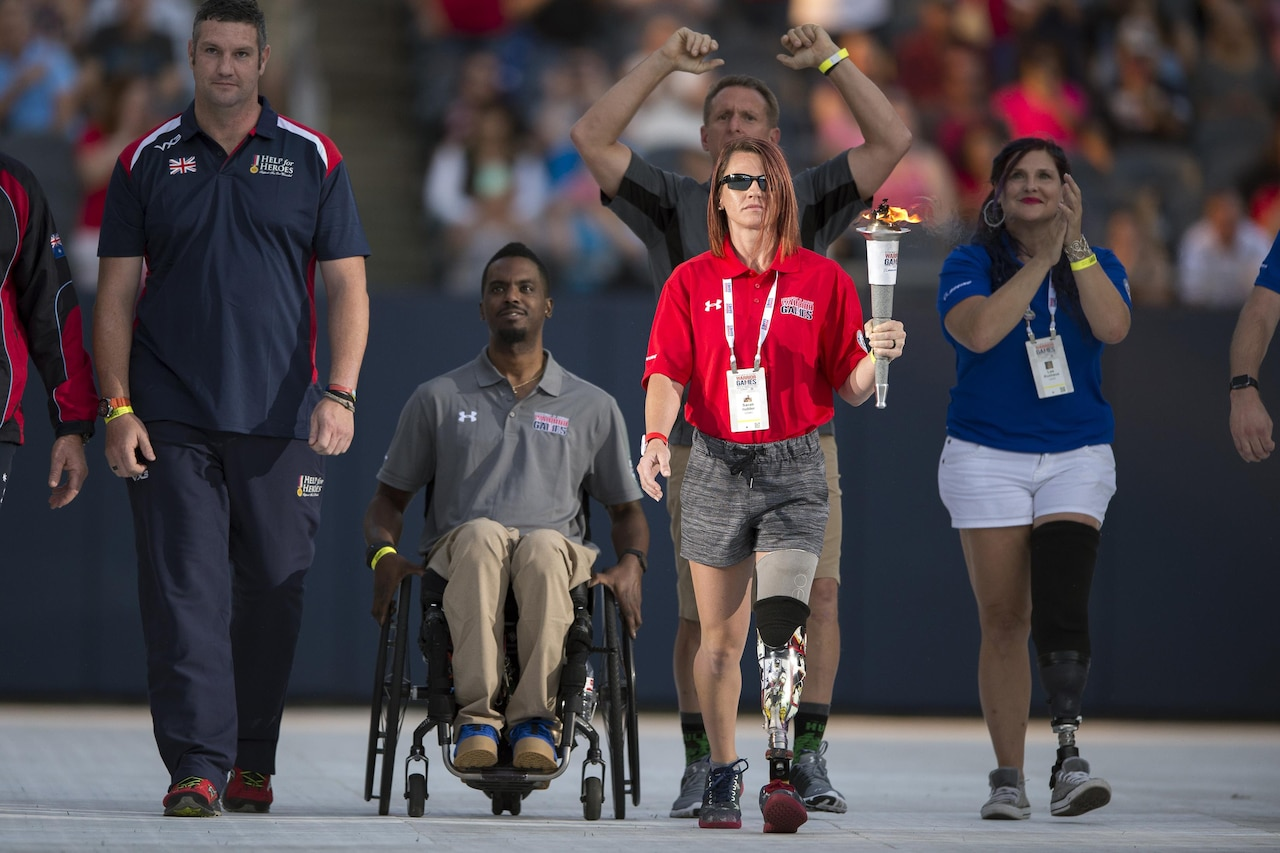 Medically retired Marine Corps Lance Cpl. Sarah Rudder carries the 2017 Department of Defense Warrior Games torch into Soldier Field in Chicago, July 1, 2017. The DoD Warrior Games are an annual event allowing wounded, ill and injured service members and veterans to compete in Paralympic-style sports. DoD photo by EJ Hersom