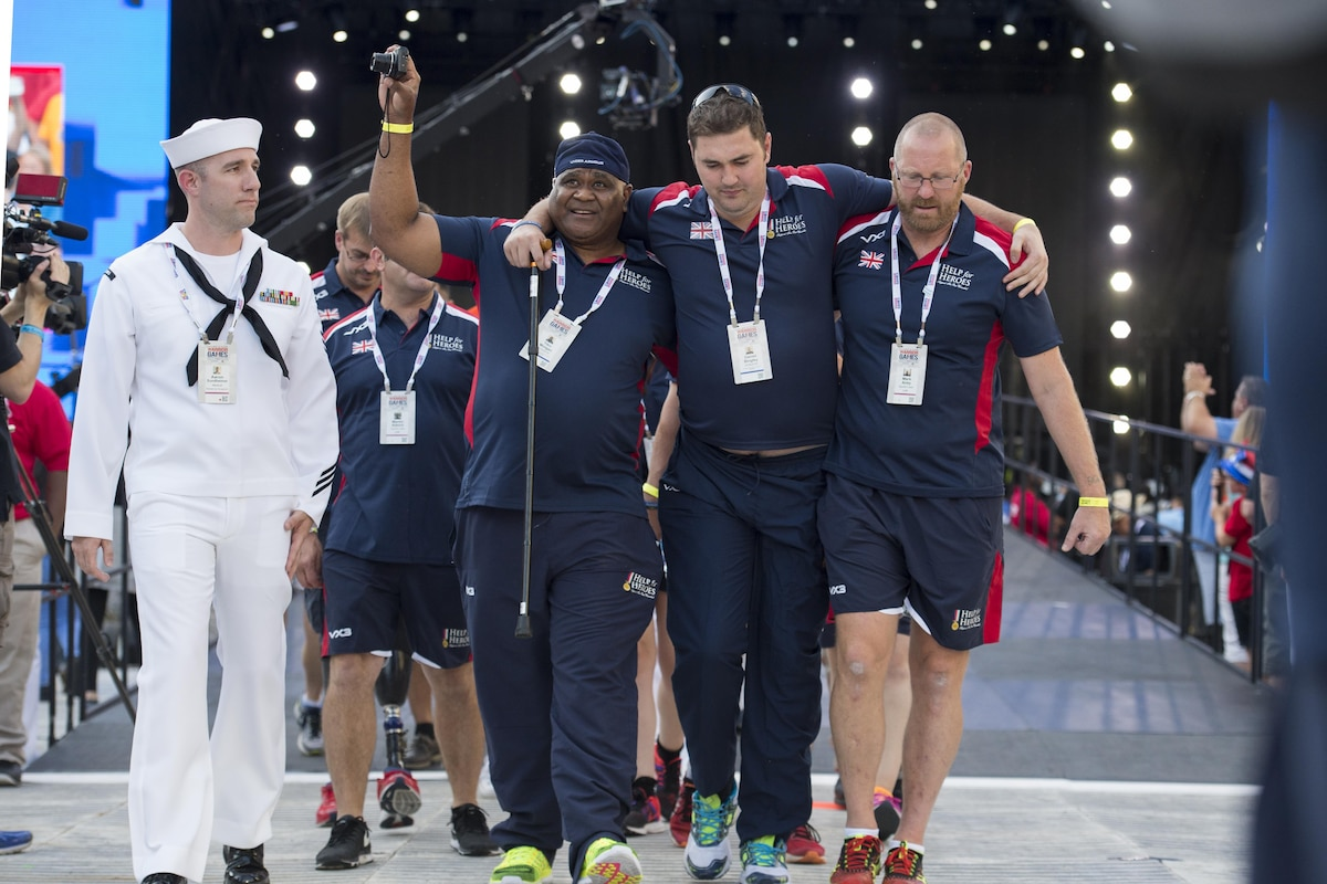Army Cpl. Tiko Morgan, left, and Mark Airey, a sports lead, help teammate Army Cpl. Daniel Bingley as team United Kingdom enters the opening ceremonies of the 2017 Department of Defense Warrior Games at Soldier Field in Chicago, July 1, 2017. DoD photo by EJ Hersom