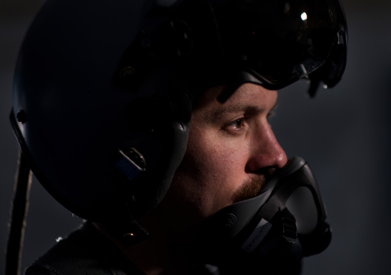 A U.S. Air Force pilot with the 332nd Air Expeditionary Wing, demonstrates the headgear aircrew must wear while flying June 13, 2017, in Southwest Asia. The Belgian Medical Component treated aircrew from the 332nd AEW for pains associated with flying high performance aircraft and weight from the equipment they carry. (U.S. Air Force photo/Senior Airman Damon Kasberg)