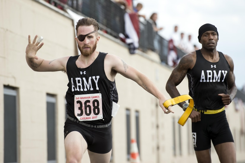 Visually impaired runner retired Army Spc. Michael Stephens finishes a race with his guide, retired Army Sgt. 1st Class Adam Blow, during the 2017 Department of Defense Warrior Games at Lane Technical College Preparatory High School in Chicago, July 2, 2017. DoD photo by EJ Hersom