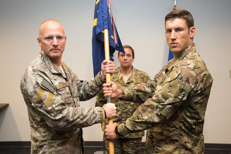POPE ARMY AIRFIELD, N.C. -- Maj. Randy Harvey (right) accepts the 21st Special Tactics Squadron guidon from Col. Spencer Cocanour, 720th Special Tactics Group commander, during a ceremony in the Airmen's Center here June 20. Harvey took command of the 21st STS from Lt. Col. Stewart Parker, and comes to Pope as a recent graduate of the Air University Air Command and Staff College at Maxwell Air Force Base, Ala. (U.S. Air Force photo/Marc Barnes)