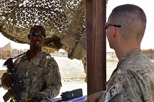 Senior Airman Sionte Campbell, 443d Expeditionary Security Forces Squadron entry controller, speaks to Capt. Jeffrey Robertson, 407th ESFS operations offficer June 22, 2017, at Al Asad Air Base, Iraq. Robertson visited security forces members at Al Asad to check on his Airmen forward deployed there and the current status and capabilities of the unit to accomplish the mission.