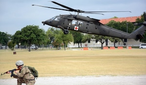 A Soldier assigned to the AMEDDC&S Training Support Activity defends while a UH-60 MEDEVAC lands to transport the wounded at Joint Base San Antonio-Fort Sam Houston June 30.