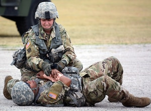 Combat medic Sgt. 1st Class Ashley Gilbert, from the Army Medical Department Non Commissioned Offers Academy, asseses the condition of an injured Soldier at Joint Base San Antonio-Fort Sam Houston June 30.