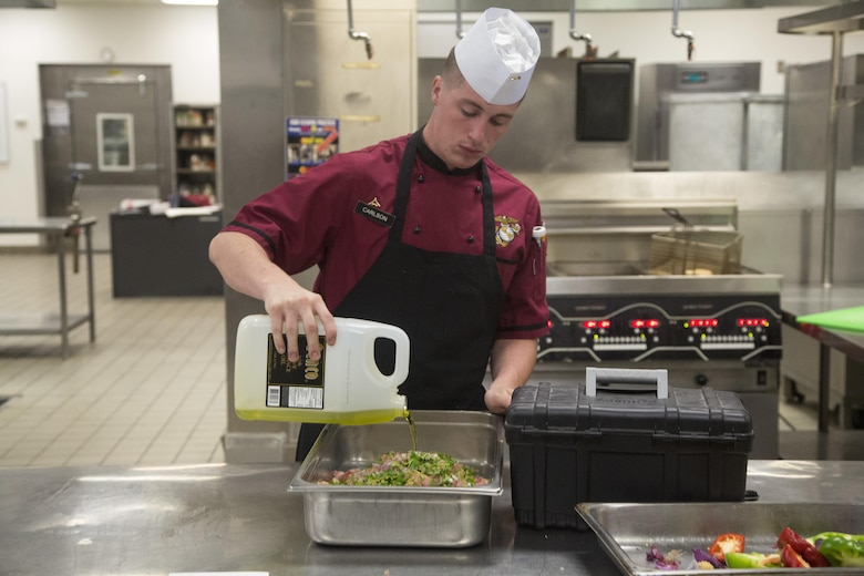 Lance Cpl. Brandon Carlson, Chef of the Quarter participant, readies chicken to be cooked for his team's meal during the Chef of the Quarter competition at Phelps Mess Hall aboard Marine Corps Air Ground Combat Center, Twentynine Palms, Calif., June 21, 2017. The competition gave Marines and Sodexo chefs the ability to cook against each other in a friendly competition and break away from the very ridged routine schedule. (U.S. Marine Corps photo by Cpl. Thomas Mudd)