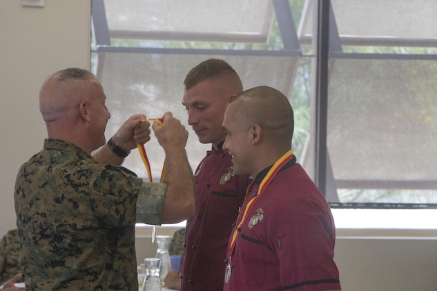 Lance Cpl. Carlos Amaya and Cpl. Tyler Faaborg, receive medals for winning the Chef of the Quarter competition at Phelps Mess Hall aboard Marine Corps Air Ground Combat Center Twentynine Palms, Calif., June 21, 2017. The team won both the Peoples' Choice and the Judges' Choice awards for this iteration of the competition. (U.S. Marine Corps photo by Cpl. Thomas Mudd)