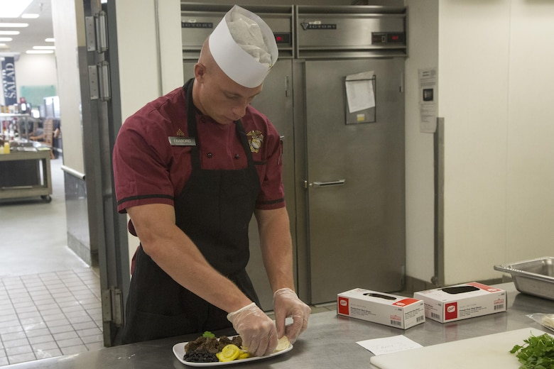 Cpl. Tyler Faaborg, Chef of the Quarter participant, readies one of his team's dishes for judging during the Chef of the Quarter competition at Phelps Mess Hall aboard Marine Corps Air Ground Combat Center Twentynine Palms, Calif., June 21, 2017. The competition gave Marines and Sodexo chefs the ability to cook against each other in a friendly competition and break away from the very ridged routine schedule. (U.S. Marine Corps photo by Cpl. Thomas Mudd)