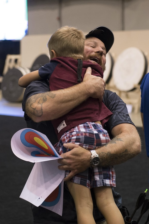 Finn Lindstrom, 8, greets his father medically retired Army Sgt. First Class Joshua Lindstrom of Team Special Operations Command after Joshua won gold during the 2017 Department of Defense Warrior Games archery competition in Chicago, July 3, 2017. The Warrior Games are an annual event allowing wounded, ill and injured service members and veterans to compete in Paralympic-style sports. DoD photo by EJ Hersom