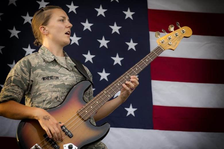 Staff Sgt. Emily Wheaton, Pacific Air Force Band member, plays a guitar during a concert at the Celebrate America festival on Yokota Air Base, Japan, June 30, 2017. The day kicked off with the firecracker 5K run and a wide variety of activities to include a petting zoo, dance performaces, food and fireworks. (U.S. Air Force photo by Staff Sgt. David Owsianka)