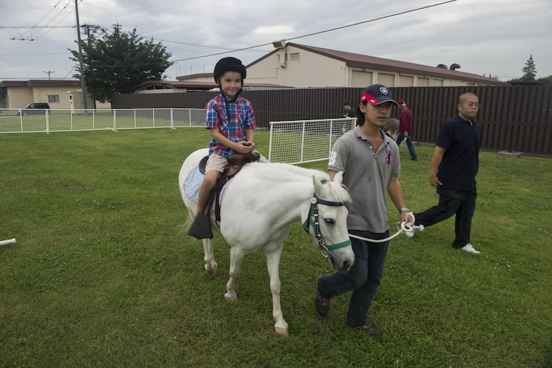 Jaxson Buum, 7, son of Tech. Sgt. Anthony Buum, 374th Aircraft Maintenance Squadron, rides a pony during the Celebrate America festival at Yokota Air Base, Japan, June 30, 2017.  The event provided military members and their families the opprotunity to enjoy games, food and bands before culminating in a fireworks display to celebrate Indepence Day. (U.S. Air Force photo by Staff Sgt. David Owsianka)