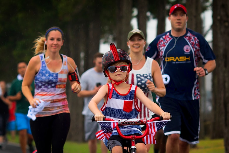 A child rides a patriotic themed bicycle during the Firecracker 5K run at Yokota Air Base, Japan, June 30, 2017. The 374th Force Support Squadron hosted events throughout the day to include a 5K Fun Run, the Leaky Son-Tiki race, cookie contest, live performances, water balloon toss, and fireworks. (U.S. Air Force photo by Yasuo Osakabe)