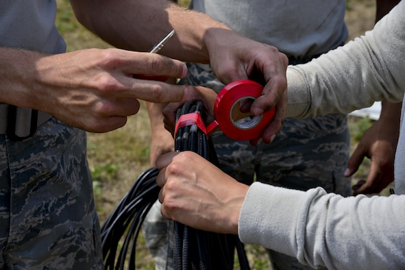 The 51st Operations Support Squadron Air Traffic Control Airfield Landing Systems personnel tape a cable at Osan Air Base, Republic of Korea, June 22, 2017. Members of Team Osan's 51st OSS and 51st Civil Engineer Squadron worked together to move an instrument landing system from the recently closed runway to the newly repaired runway. (U.S. Air Force photo by Airman 1st Class Gwendalyn Smith)