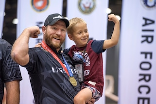 Retired Army Sgt. 1st Class Joshua Lindstrom of Team Special Operations Command, celebrates with his son Finn James Lindstrom, 8, after winning gold in compound archery during the 2017 Department of Defense Warrior Games in Chicago, July 3, 2017. DoD photo by Roger L. Wollenberg