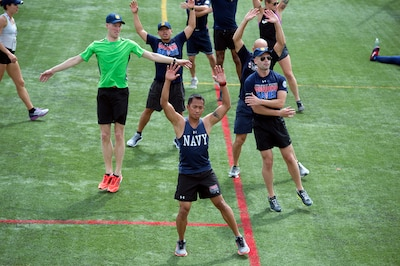 Navy Petty Officer 1st Class Romulo Urtula, front, leads a warm up exercise during track practice for the 2017 Department of Defense Warrior Games in Chicago, June 30, 2017. DoD photo by EJ Hersom