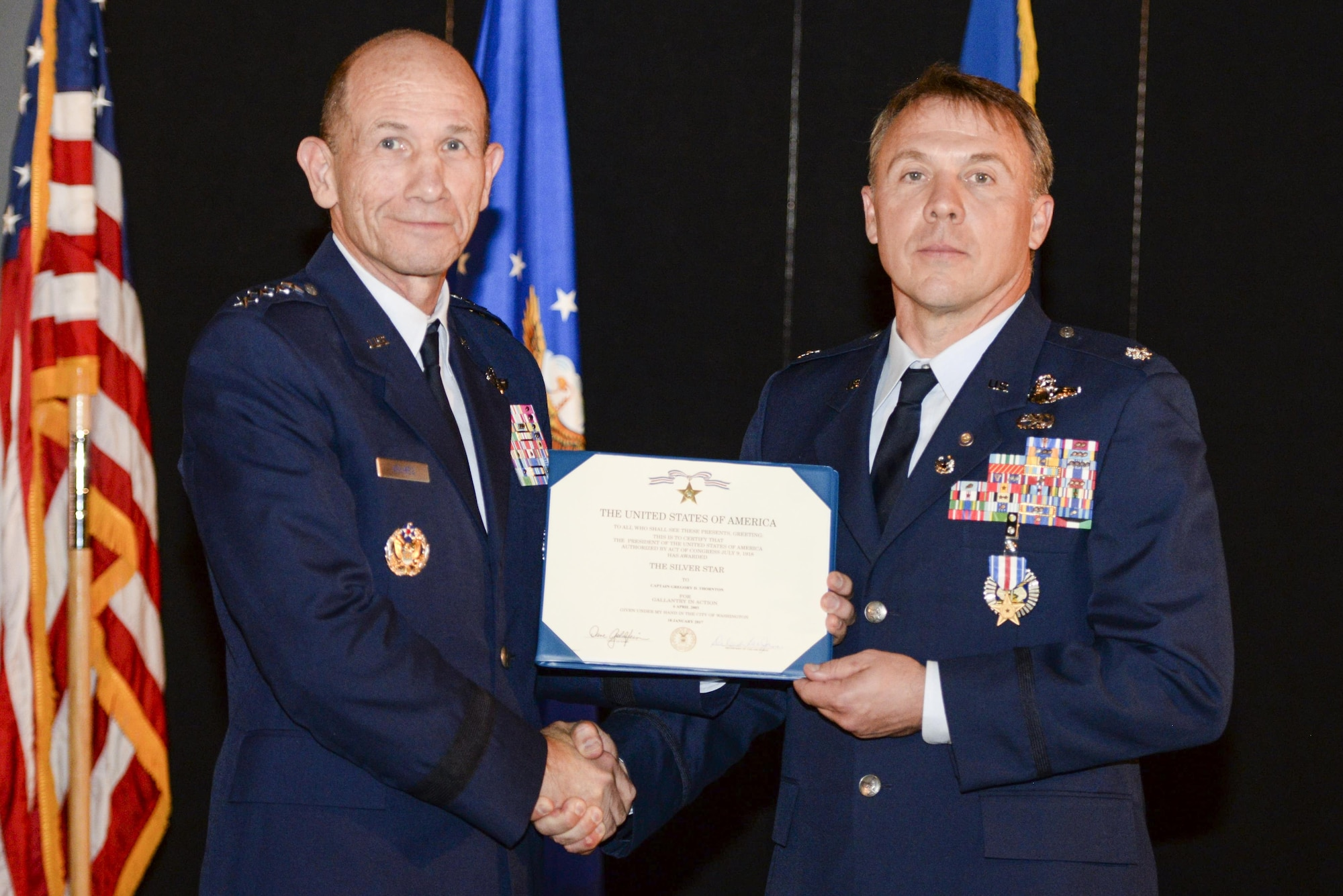U.S. Air Force Gen. Mike Holmes, commander, Air Combat Command, presents retired Air Force Lt. Col. Gregory Thornton with the Silver Star medal certificate during a ceremony at the National Museum of the United States Air Force in Dayton, Ohio, June 30, 2017. Thornton received the Silver Star for his actions on April 6, 2003 while supporting 'Advance 33,' the call sign for a ground forward air controller attached to Task Force 2nd Battalion, 69th Armor, during combat operations in Iraq. The Silver Star is the third-highest combat decoration for gallantry in action that can be awarded to a member of the United States Armed Forces. (U.S. Air Force photo by Wesley Farnsworth)