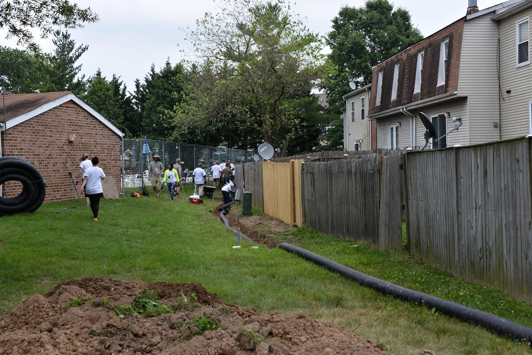 Volunteers from the 70th Intelligence, Surveillance and Reconnaissance Wing, National Capitol Region service members, Rebuilding Together Ann Arundel County and CBRE dig a canal to create a French drain to clear a standing water issue for a neighborhood June 16, 2017 Bowie, Md. In a recent initiative, RTAAC created a three-year project to repair homes for low-income residents in need within the county with the help of over 200 volunteers from the area. (U.S. Air Force photo/Staff Sgt. Alexandre Montes)