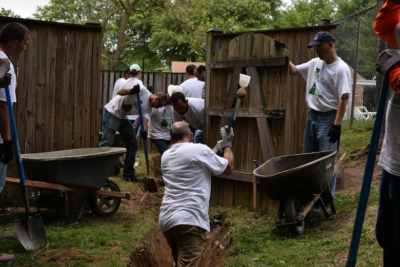 Volunteers from the 70th Intelligence, Surveillance and Reconnaissance Wing, National Capitol Region service members, Rebuilding Together Ann Arundel County and CBRE dig a canal to create a French drain to clear a standing water issue for a neighborhood June 16, 2017 in Bowie, Md. In a recent initiative, RTAAC created a three-year project to repair homes for low-income residents in need within the county with the help of over 200 volunteers from the area. (U.S. Air Force photo/Staff Sgt. Alexandre Montes)