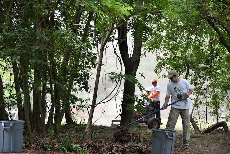 Volunteers from the 70th Intelligence, Surveillance and Reconnaissance Wing, National Capitol Region service members, RTAAC and CBRE remove debris and mow the lawn in a park June 16, 2017 in Bowie, Md. In a recent initiative, Rebuilding Together Ann Arundel County (RTAAC), a non-profit organization, created a three-year project to repair homes for low-income residents in need within the county. (U.S. Air Force photo/Staff Sgt. Alexandre Montes)