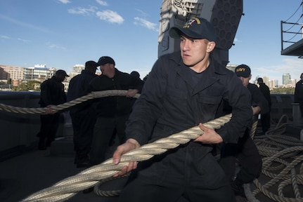 Seaman Apprentice Alex Ponce, from Morrilton, Ark., heaves a mooring line on the fantail of the amphibious assault ship USS Bonhomme Richard (LHD 6), July 3, 2017, as the ship departs Sydney following a four-day port visit and prepares to participate in Talisman Saber 2017. Talisman Saber is a biennial U.S.-Australian bilateral military exercise that combines a field training exercise and command post exercise to strengthen interoperability and response capabilities to uphold the tenets of the U.S.-Australian alliance.