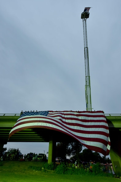 Goodfellow Air Force Base service members hold an American flag during the 30th Annual San Angelo Symphony July 3rd Pops Concert at the Bill Aylor Sr. Memorial RiverStage in San Angelo, Texas, July 3, 2017. The San Angelo Fire Department also hung their own flag for the event. (U.S. Air Force photo by Staff Sgt. Joshua Edwards/Released)