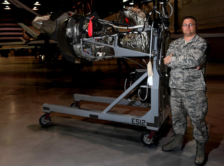 Master Sgt. Eric, 432nd Aircraft Maintenance Squadron Reaper Aircraft Maintenance Unit production superintendent, stands with the engine trainer he created June 19, 2017, at Creech Air Force Base, Nev. He saw a need to have a power capable training engine to practice engine rigging, which involves tuning the actuators that translate electrical signals to mechanical commands. If done improperly the engine can shutoff when not intended. The trainer allowed maintainers to train on this vital task without taking an operational aircraft out of the rotation. (U.S. Air Force photo/Senior Airman Christian Clausen)