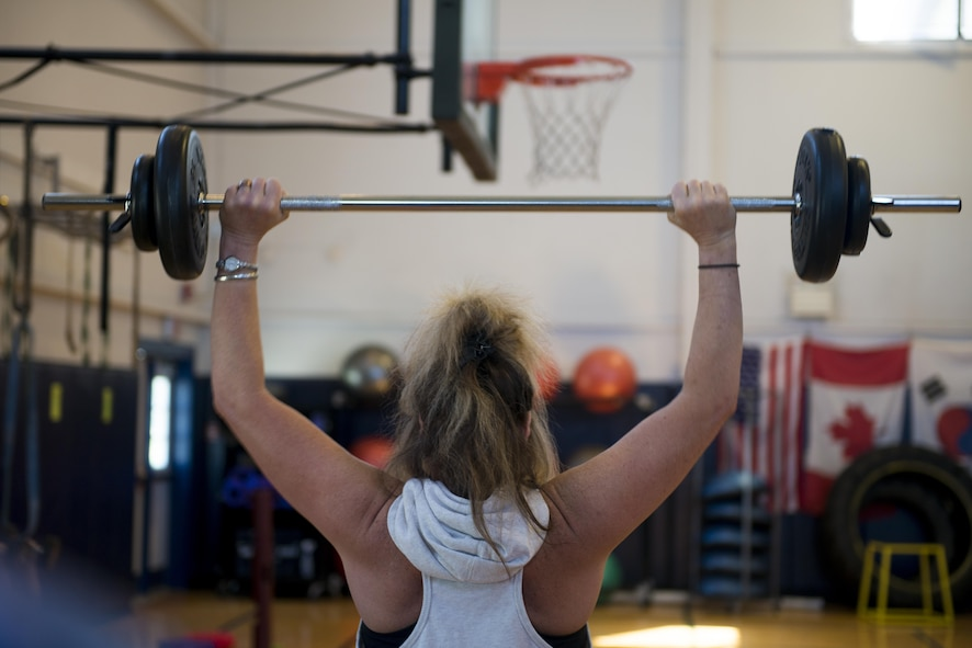 Gracie Poitras lifts weights above her head during a Wellbeats class held at the fitness center, July 5, 2017, Niagara Falls Air Reserve Station, N.Y. Fitness classes are held throughout the week here, focusing on cardio and strength training. (U.S. Air Force photo by Tech. Sgt. Stephanie Sawyer)