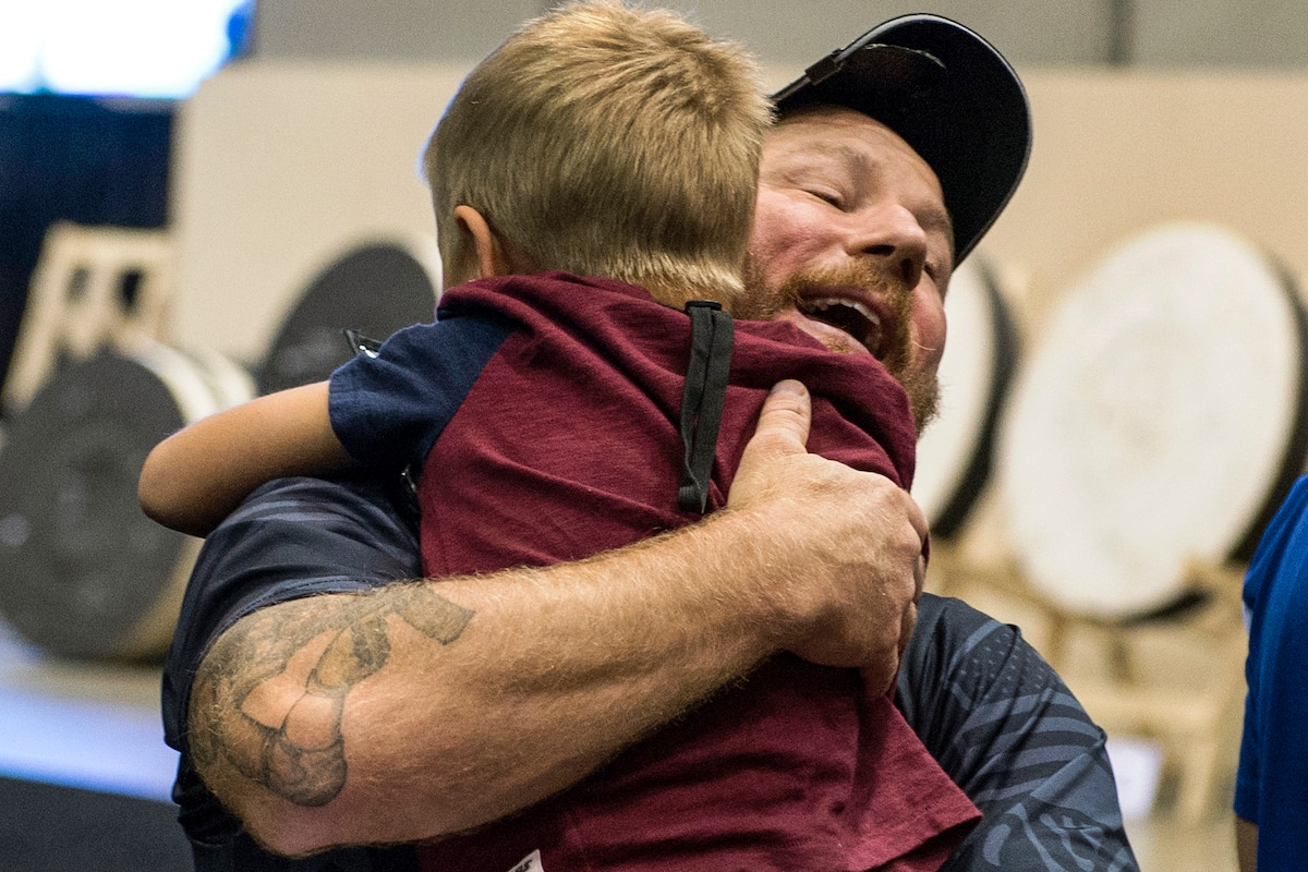An Army veteran hugs his 8-year-old son after winning gold in an archery event.