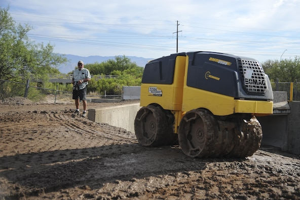 Douglas Burke, 355th Civil Engineer Squadron heavy equipment operator, remotely controls a sheepsfoot roller to flatten dirt at Davis-Monthan Air Force Base, Ariz., June 8, 2017. The 355th Civil Engineer Squadron pavements and equipment shop used approximately 2,500 tons of dirt to help reconstruct Atterbury Wash, a natural creek on the installation, in preparation for monsoon season. (U.S. Air Force photo by Senior Airman Mya M. Crosby)