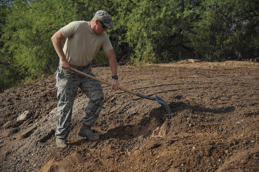 U.S. Air Force Staff Sgt. Chad McCay, 355th Civil Engineer Squadron pavements and equipment craftsman, shovels dirt at Davis-Monthan Air Force Base, Ariz., June 8, 2017. The 355th Civil Engineer Squadron pavements and equipment shop used approximately 2,500 tons of dirt to help reconstruct Atterbury Wash, a natural creek on the installation, in preparation for monsoon season.  (U.S. Air Force photo by Senior Airman Mya M. Crosby)