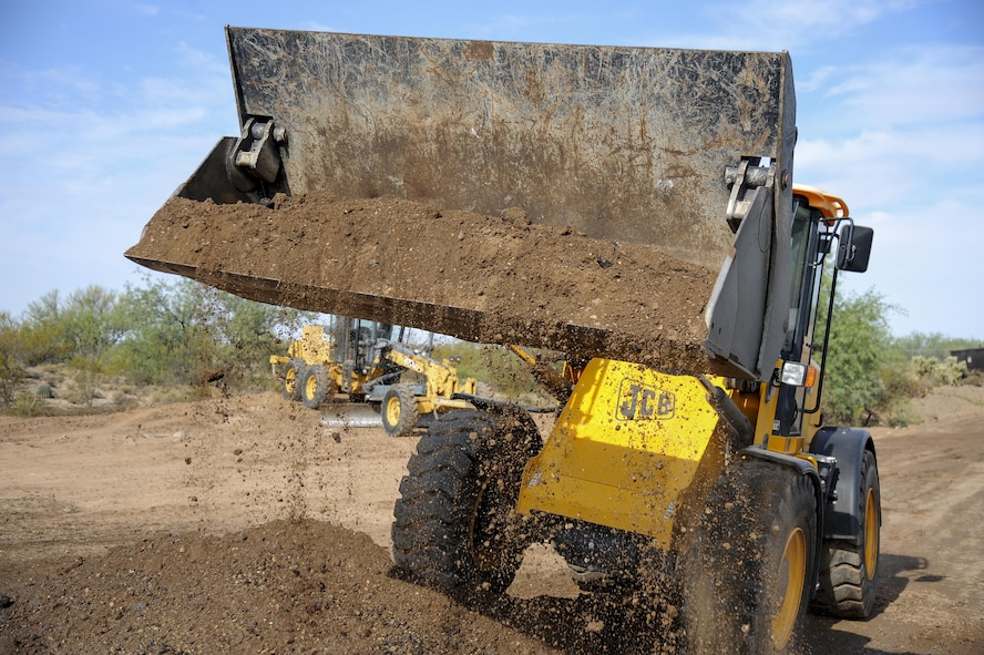 A front-end roller shovels dirt at Davis-Monthan Air Force Base, Ariz., June 8, 2017. The 355th CES Airmen from the pavements and equipment shop were reconstructing a permanent foundation for Atterbury Wash, a key element to the monsoon season for the installation and local Tucson community. (U.S. Air Force photo by Senior Airman Mya M. Crosby)