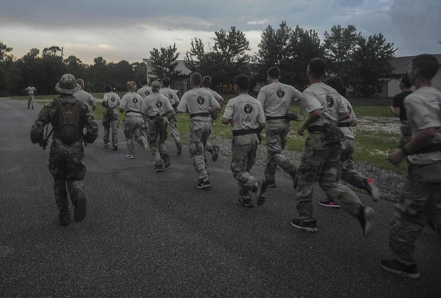 A Special Tactics Airman with the 23rd Special Tactics Squadron leads Junior ROTC cadets on a formation run toward an obstable during a Monster Mash at Hurlburt Field, Fla., June 30, 2017. A Monster Mash is a competition designed to strengthen team-building and leadership skills. (U.S. Air Force photo by Airman 1st Class Rachel Yates)