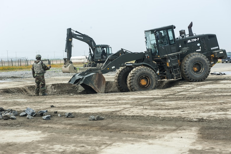 U.S. Air Force Tech. Sgt. Freeman Gleaves, 8th Civil Engineering Squadron pavement and construction craftsman, directs how much gravel to pour into a simulated runway crater during an exercise June 29, 2017, at Kunsan Air Base, Republic of Korea. The airfield damage repair exercise gave Airmen an opportunity to test their ability to map runway damage and plot the best course of action to fix that damage in the shortest possible time. (U.S. Air Force photo by Senior Airman Colville McFee/Released)