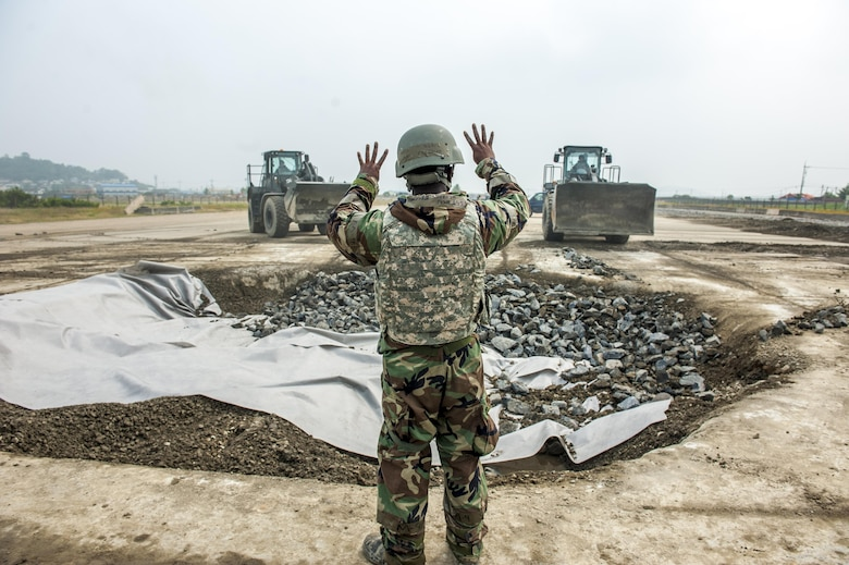 U.S. Air Force Tech. Sgt. Freeman Gleaves, 8th Civil Engineering Squadron pavement and construction craftsman, communicates with two loaders June 29, 2017, at Kunsan Air Base, Republic of Korea. The CES Airmen were tasked with repairing a damaged portion of the runway while participating in an airfield damage repair exercise. (U.S. Air Force photo by Senior Airman Colville McFee/Released)