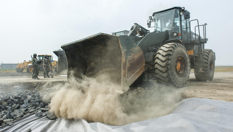 U.S. Air Force Airmen assigned to the 8th Civil Engineering Squadron pavement and construction section, stand by to assist a loader as it unloads rocks into a crater June 29, 2017, at Kunsan Air Base, Republic of Korea. The crater simulated runway battle damage, preventing aircraft takeoff. CES airmen were tasked to repair the damage as quickly as possible during an airfield damage repair exercise. (U.S. Air Force photo by Senior Airman Colville McFee/Released)