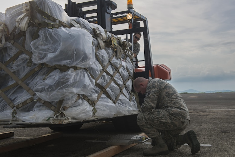 From left, Tech. Sgt. Phillip Eyer, 374th Logistics and Readiness Squadron joint inspector, and Staff Sgt. Brandon Inhat, 374 LRS flight combat mobility operations technician, inspect a cargo pallet during Yokota Air Base's first C-130J Super Hercules operational mission, June 30, 2017, at Manila, Philippines. The mission highlighted Yokota's C-130J increased airlift capabilities. (U.S. Air Force photo by Airman 1st Class Juan Torres)