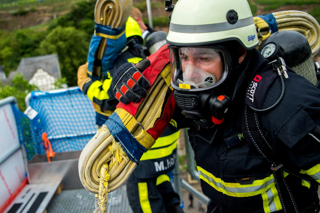 A firefighter from Germany carries a hose while racing against an opponent during the 4th annual Mosel Firefighter Combat Challenge in Ediger-Eller, Germany, June 30, 2017. During the first obstacle of the competition, a 42 pound hose must be carried up a five-story tower with fire protective gear on including gloves, mask, helmet, coat, pants, boots and an air pack. (U.S. Air Force photo by Senior Airman Preston Cherry)