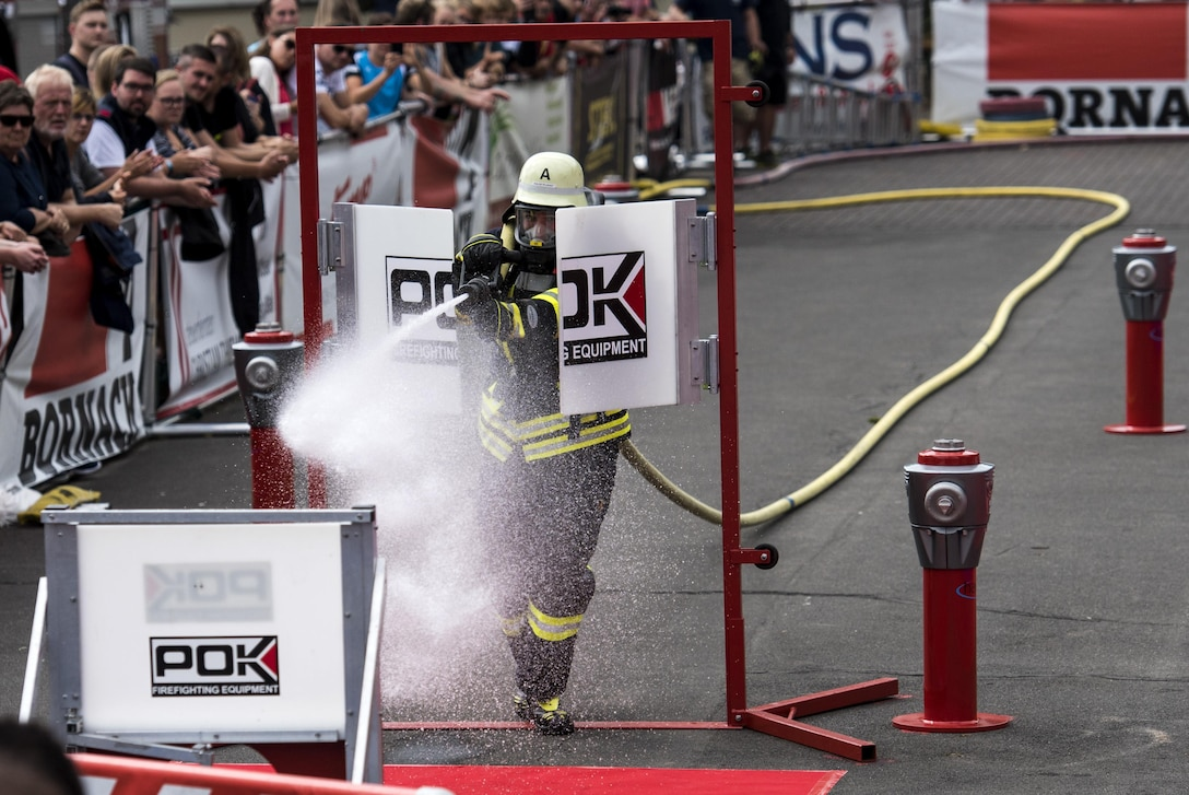 A German firefighter uses a hose to knock down a target during the 4th annual Mosel Firefighter Combat Challenge in Ediger-Eller, Germany, June 30, 2017. Competitors from 12 countries raced head-to-head as they performed challenges to simulate real-life firefighting scenarios including a five-story tower climb, hoisting, chopping, extinguishing, dragging hoses and rescuing a 175 pound mock victim. (U.S. Air Force photo by Senior Airman Preston Cherry)